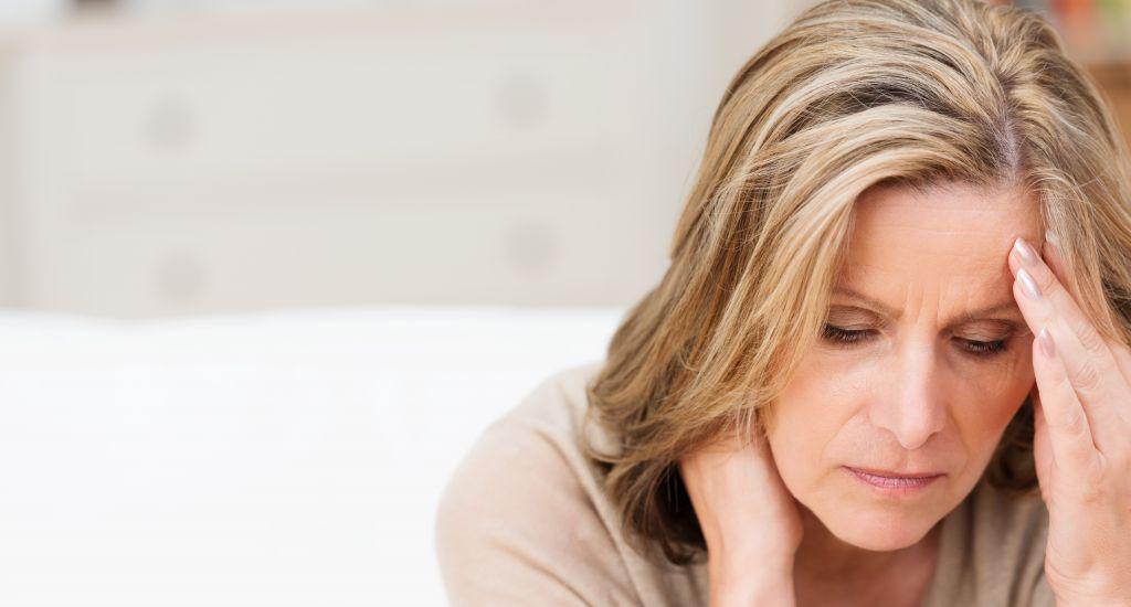 Psychosomatische Schmerzen, Frau mit Rücken- und Kopfschmerzen